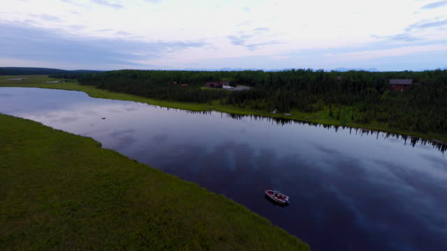 4k high resolution aerial birds eye view drone tracking shot of glass calm and reflective Moose River with single boat on it and tracking toward the other river bank with a house in the green pine forest. video