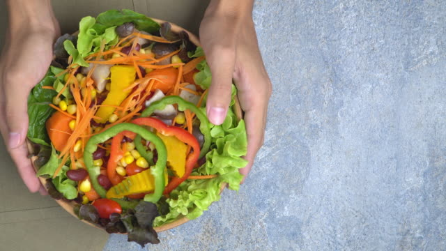 vídeos de stock e filmes b-roll de 4k holding and lay salad bowl on blue background. - saladeira