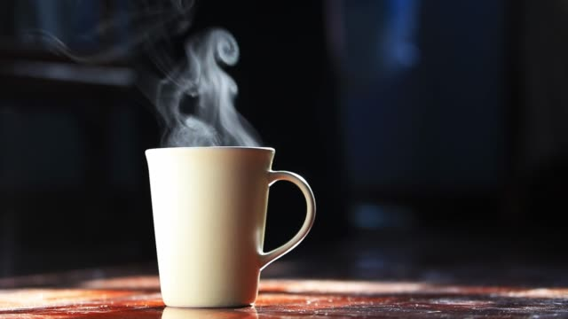 4k Hot smoke over home brew espresso coffee cup on the dark background by the morning light