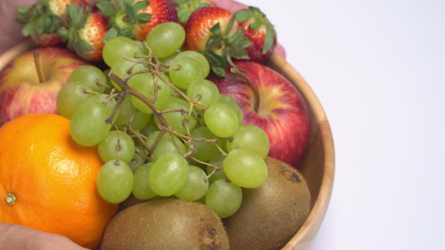 vídeos de stock e filmes b-roll de 4k human hand lay fruit bowl on white background. - saladeira