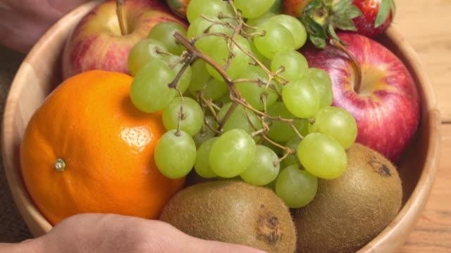 vídeos de stock e filmes b-roll de 4k human hand lay fruit bowl on wooden background. - saladeira