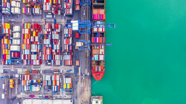 4k, Hyper lapse aerial view container ship loading and unloading in deep sea port, Aerial top view of logistic import export transportation business by container ship in open sea.