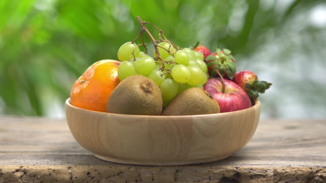 vídeos de stock e filmes b-roll de 4k mix fruit in wooden bowl with green bokeh background. - saladeira
