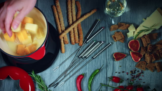4k mixed cheese fondue adding cheddar cubes - french food stock videos and b-roll footage