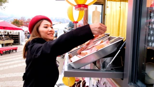 日本マーケットでのフード トラックから焼き鳥 (豚肉グリル) を選択するアジア女性の 4 k 動画撮影 - 飲食店点の映像素材/bロール