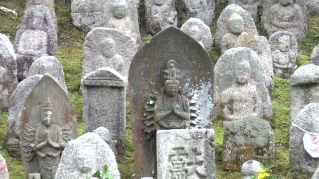 4k: multiple buddha statues at shrine - gambe incrociate video stock e b–roll