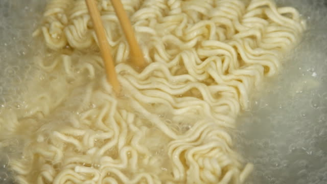 4k of chopsticks stirring cooking instant noodles in frying pan video