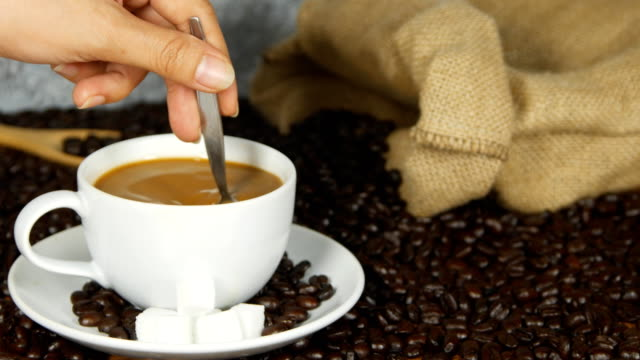 4k of Close-up female hand mixing sugar in coffee cup video