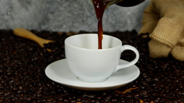 4k of Pouring coffee from coffee pot in white cup surrounded by coffee beans video