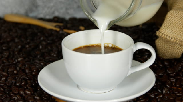 4k of Pouring milk into a cup of coffee video