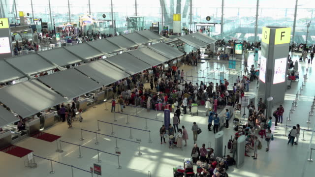 4k: passengers wait at the check in queue in departure terminal of bangkok suvarnabhumi airport - аэровокзал стоковые видео и кадры b-roll