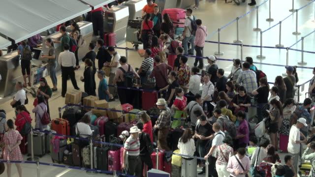 4k: passagiere warten am check-in warteschlange im abflugterminal des bangkok suvarnabhumi airport - hart arbeiten stock-videos und b-roll-filmmaterial
