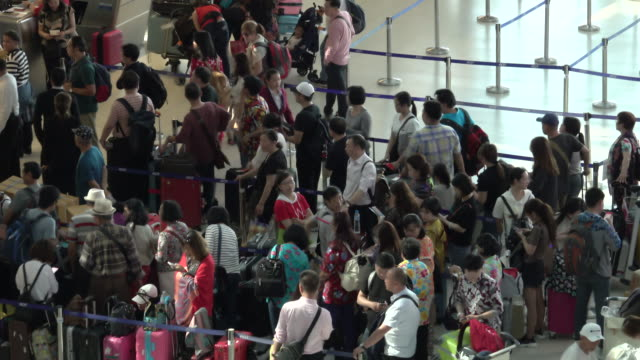 vidéos et rushes de 4k: passagers attendent lors du contrôle dans la file d'attente dans le terminal de départ de l'aéroport de bangkok suvarnabhumi - faire la queue