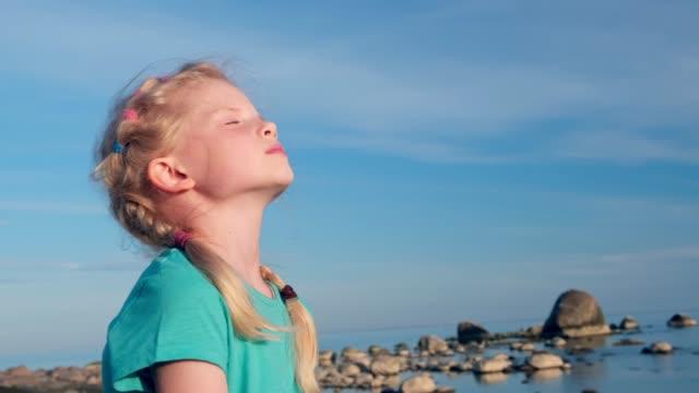 vídeos de stock, filmes e b-roll de 4k. garota relaxada respirando ar fresco sobre o céu azul no mar no verão. sonhando, liberdade e conceito de viagem - braço humano