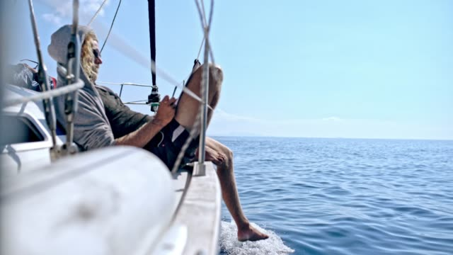 4k resolution, adventure, at the edge of, barefoot, blue, carefree, discovery, enjoyment, exploration, freedom, getting away from it all, hanging, healthy lifestyle, idyllic, journey, leg, low section, medium shot, mid adult, mid adult men, nautical vesse 4K Man relaxing, doing crossword puzzle on sunny sailboat. MS, real time. recreational boat stock videos & royalty-free footage