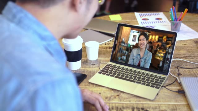 4k resolution Asian man and woman say hello during online video call via laptop computer in coffee shop