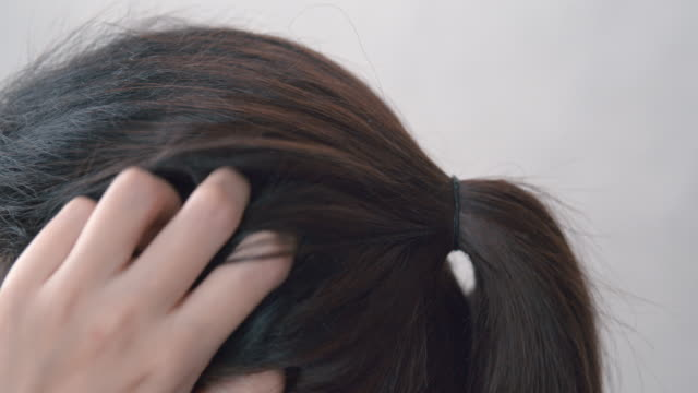 4k resolution Asian woman itchy and scratching scalp damaged hair on her head. Haircare concept