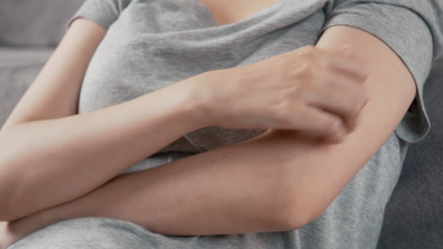 4k resolution Asian Woman scratching on her arm while working at home office.