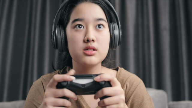 4k resolution attractive asian girl wearing wireless headphone holding joystick or game controller and playing online video game console at home. kid upset or anger to play a game while stay at home with coronavirus lockdown situation - cuffie wireless video stock e b–roll