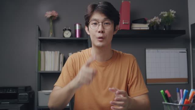 vidéos et rushes de 4k résolution attrayante professeur d'homme asiatique expliquant les devoirs de mathématiques à son étudiant en ligne sur la vidéoconférence. il utilise la technologie d'appel vidéo en ligne enseignant la formule mathématique de la maison tandi - conférence en ligne