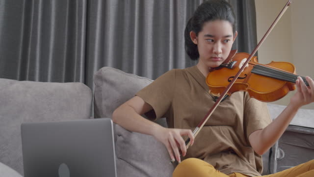 4k resolution Attractive Asian teen girl practice and learning violin online lesson with her teacher by using laptop computer while stay at home from coronavirus lockdown situation.Young woman playing classical Music instrument.