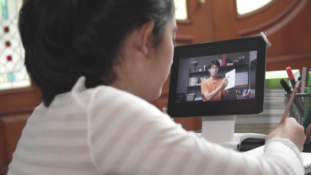4k resolution attractive asian teenager girl studying with her teacher e-learning on tablet screen with online homeschool while coronavirus or covid 19 lockdown situation. video call technology with her advice to learn her homework. - дистанционный стоковые видео и кадры b-roll