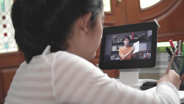 stockvideo's en b-roll-footage met 4k resolutie aantrekkelijke aziatische tiener meisje studeren met haar leraar e-learning op tablet scherm met online homeschool, terwijl coronavirus of covid 19 lockdown situatie. video gesprek technologie met haar advies om haar huiswerk te leren. - ver