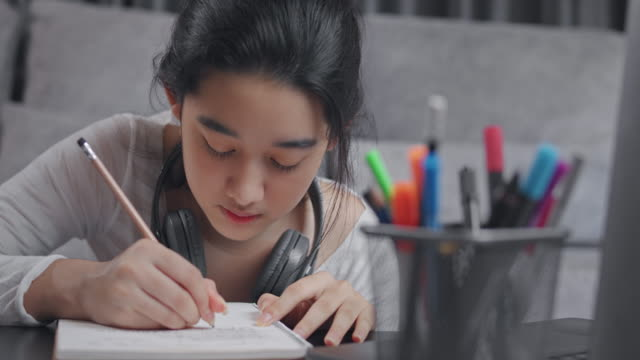 4k resolution attractive asian teenager girl studying with her teacher e-learning on laptop with online homeschool in the living room while coronavirus or covid 19 lockdown situation. Video call technology with her advice to learn her homework.
