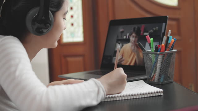 stockvideo's en b-roll-footage met 4k resolutie aantrekkelijke aziatische tiener meisje het dragen van een hoofdtelefoon en studeren met haar leraar e-learning op tablet scherm met online homeschool, terwijl coronavirus of covid 19 lockdown situatie. video call technologie met haar advies o - student