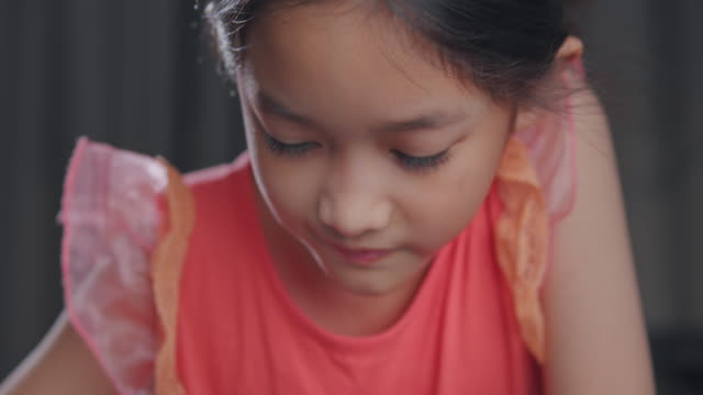 4k resolution attractive asian tween kid girl studying with her teacher e-learning on tablet screen with online homeschool while coronavirus or covid 19 lockdown situation. She having Video call technology with her advice to learn her homework.