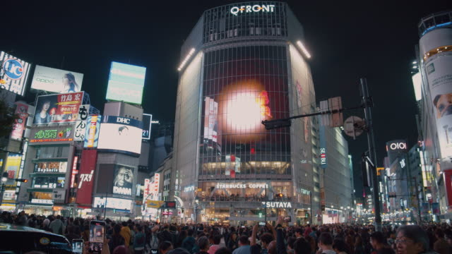 4k resolution crowed of people night life at shibuya crossing. traffic car and transportation across intersection - insegna commerciale video stock e b–roll