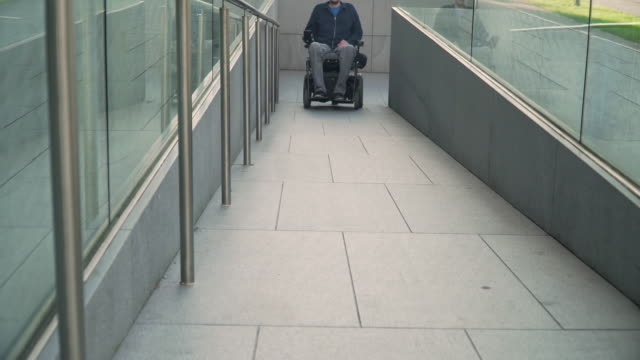 4k resolution front view of a man on electric wheelchair using a ramp. Accessibility concept