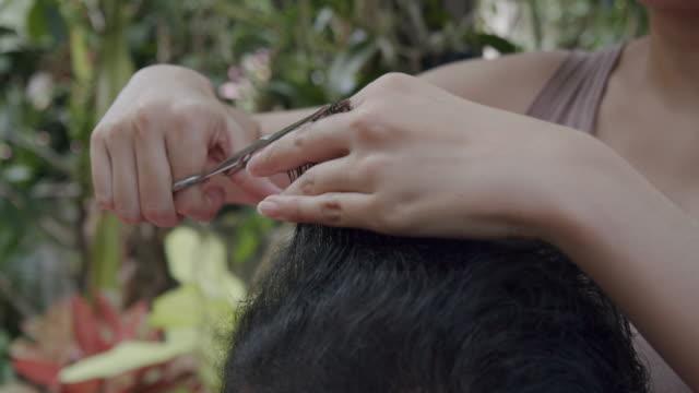 4k auflösung mit haaren geschnitten von seiner tochter, während zu hause von coronavirus situation sperre. - friseur lockdown stock-videos und b-roll-filmmaterial