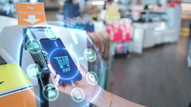 4k resolution Internet of Things and Mobile Payment concept,close up hand holding smart phone with Communication icons.Paying through terminal.Connection and wireless network Technology