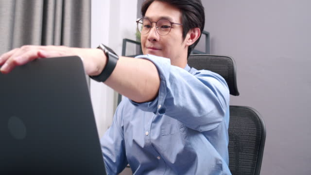 4k resolution of attractive asian man finishing on his work from home and closing laptop computer relax stretching finishing closing laptop, standing and leaving from home office desk. - surfować po internecie filmów i materiałów b-roll