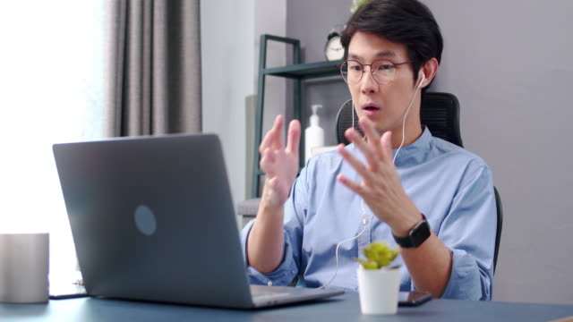 4k resolution of Attractive asian man wearing earphones having video conference or video call through laptop computer with his partnership while working from home with Coronavirus or COVID 10 Situation.