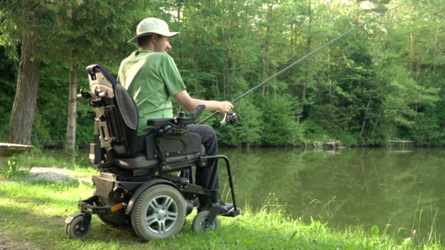 vídeos de stock e filmes b-roll de 4k resolution of happy man in a electric wheelchair fishing at the beautiful pond in natue on a sunny day - pessoas com deficiência