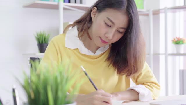 4 k resolução bastante mulher asiática sentado em sua casa e escrever um livro, o conceito de lifestyle mulher asiática - vídeo