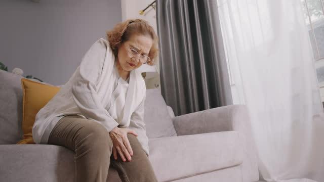 vídeos de stock, filmes e b-roll de resolução 4k mulher asiática sênior usando a mão massageando em seu joelho e dor nas pernas. ela tem lesão física. conceito de cuidados de saúde. close-up tiro. - articulação humana