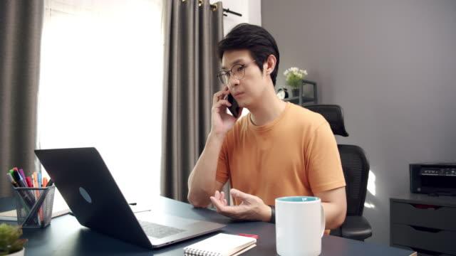 4k çözünürlük karantina coronavirus veya covid 19 durum evden çalışırken ev ofisinde dizüstü bilgisayar kullanırken akıllı telefon ortağı ile konuşurken çekici asya yetişkin adam yavaş hareket - güneydoğu asya stok videoları ve detay görüntü çekimi