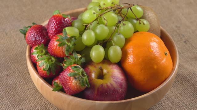 vídeos de stock e filmes b-roll de 4k rotate of mix fruit in wooden bowl. - saladeira