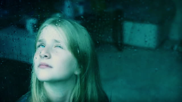 4k Sad Child Girl Looking through the Glass while Raining video