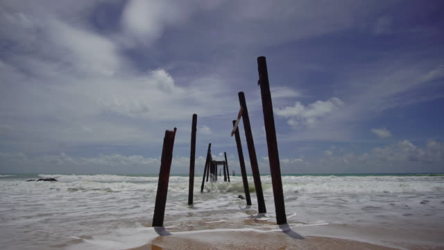 4k, Sea beach and old ruins wooden bridge with blue sky. video