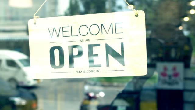 stockvideo's en b-roll-footage met 4 k shop eigenaar veranderende teken van gesloten naar open. - shop sign