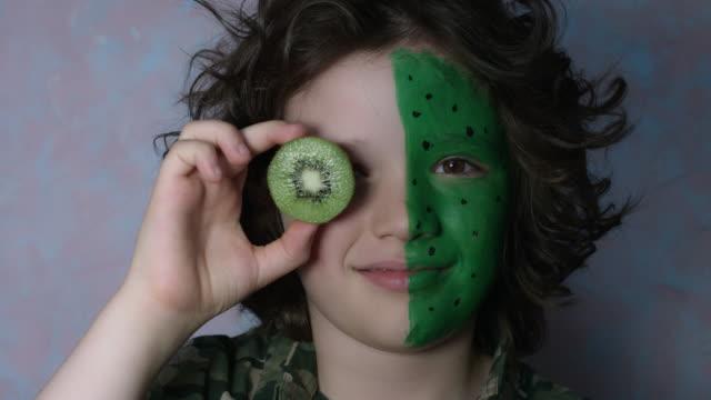 4k skjuten av en söt barn med färgade ansikte poserar med kiwi - kiwifrukt bildbanksvideor och videomaterial från bakom kulisserna