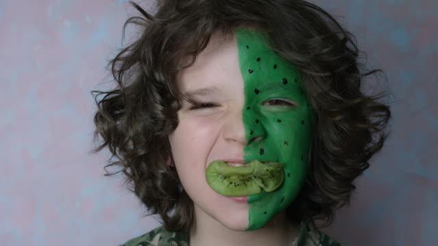 4 k skott av en söt barn med färgade ansikte klämma en kiwi i munnen - kiwifrukt bildbanksvideor och videomaterial från bakom kulisserna