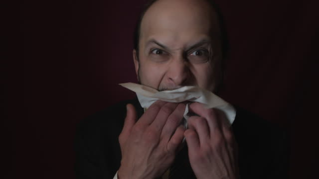 4k Shot of a Handsome Young Businessman Angry Eating a Paper