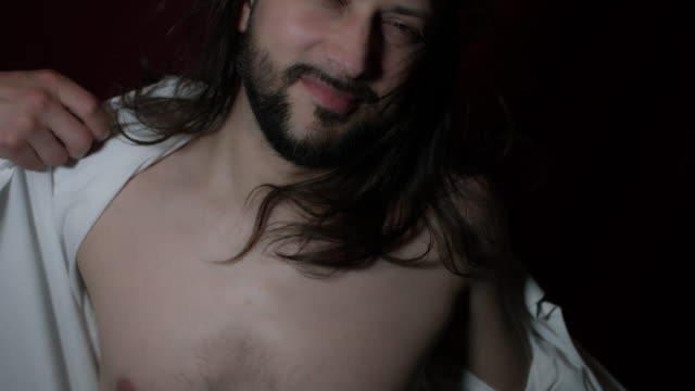 4k Shot of a Handsome Young Businessman with Long Hairs Taking off his Shirt