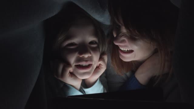 子供と毛布の下のタブレットをお探しのお母さんの 4 k 撮影 ビデオ