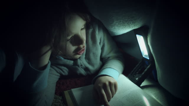 4k Shot of Child under Blanket Reading Book with Flashlight video